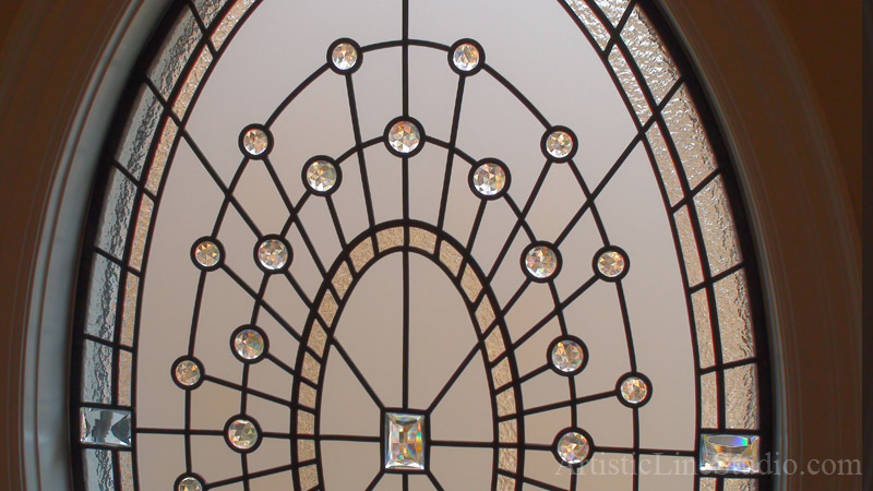 Detail of leaded glass eleptical window with crystal jewels and acid etched glass