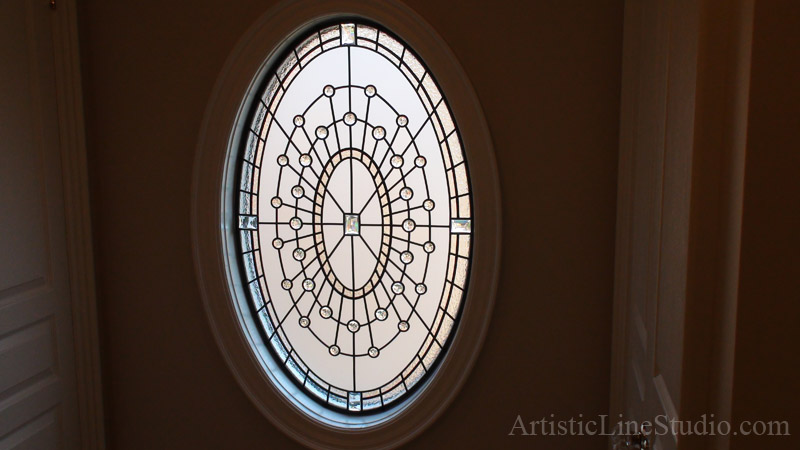 Leaded glass oval window with crystal jewels and acid etched glass to add privacy and beauty