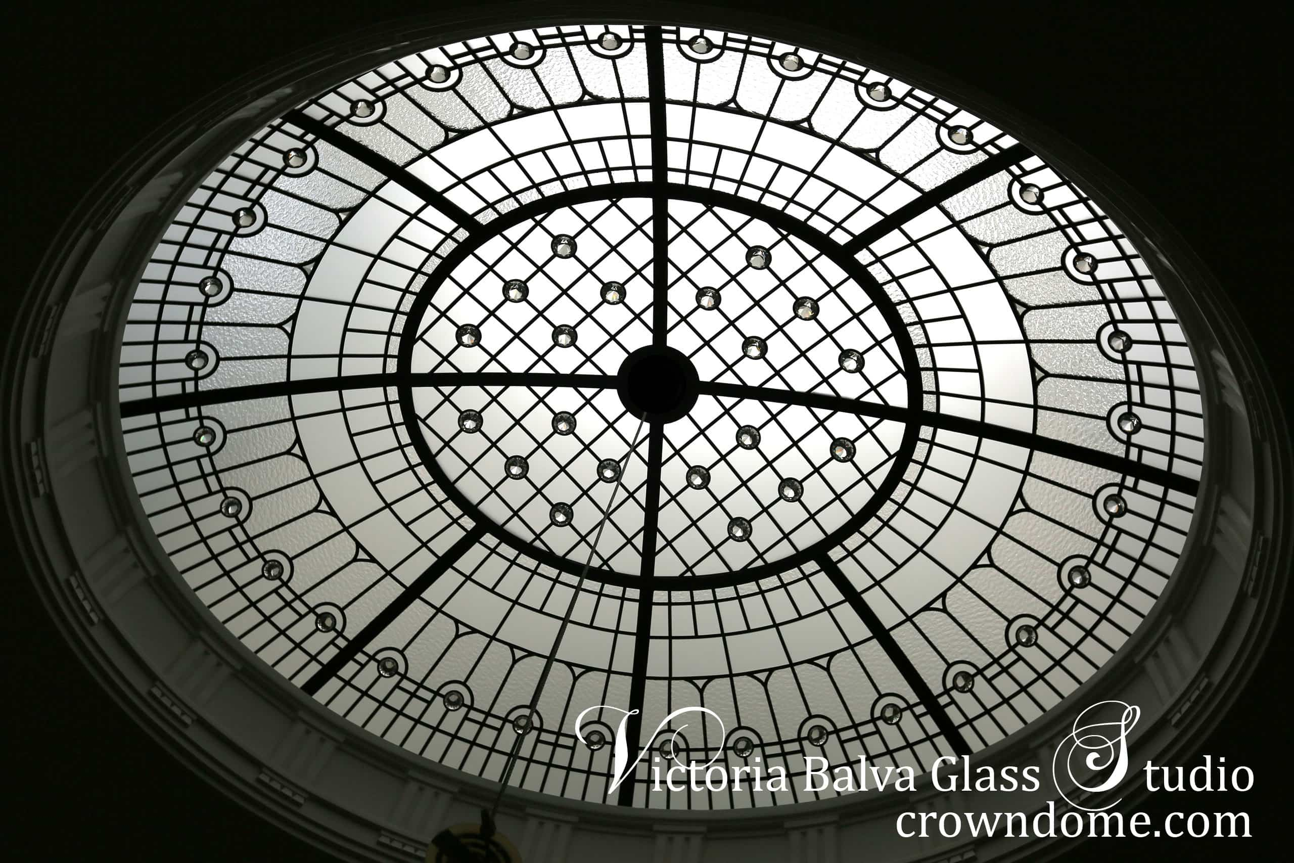Leaded glass oval dome with crystal chandelier for a stairwell of a luxury custom built residence. Crystal jewels, clear textured and beveled glass add style and beauty to the interior space of the house