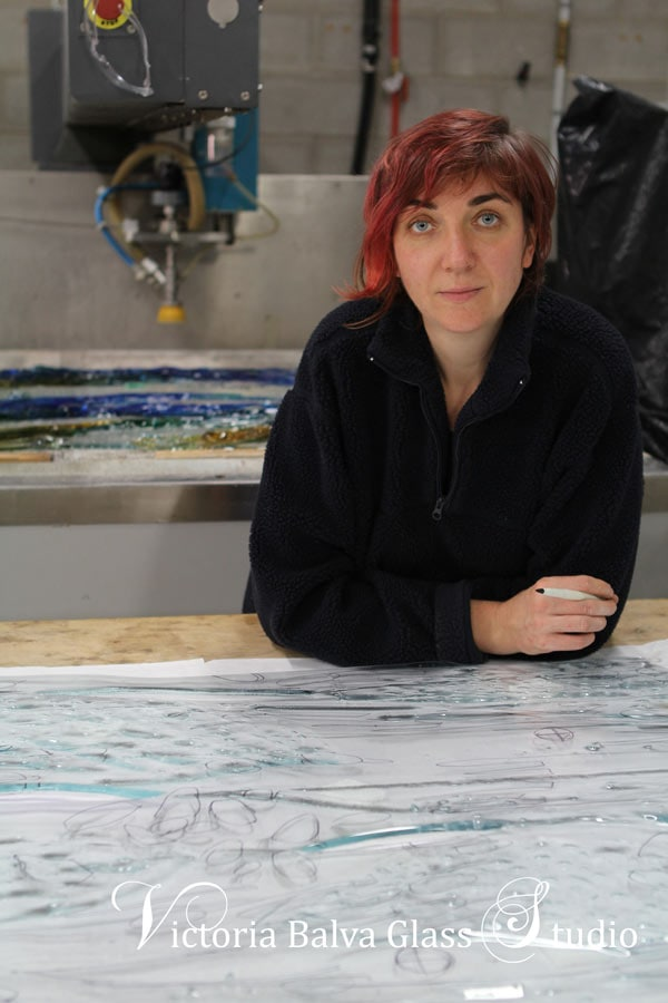 Stained leaded glass artist Victoria Balva in her architectural glass studio working on a kiln cast art glass