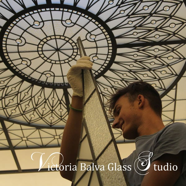 Glass studio assistant Michael Ivanov helping to install stained and leaded glass decorative skylight