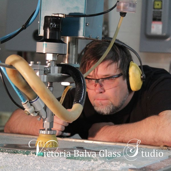 Technical assistant Eugene Bakumenko operating a water jet machine in Victoria Balva Glass Studio. Cutting art glass with waterjet machine is unforgettable experience