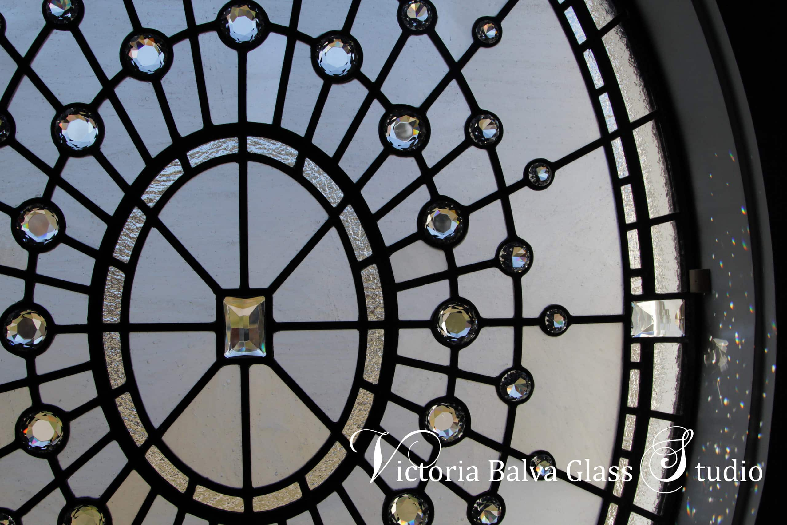 Large oval stained leaded glass window w crystal jewel accents for staircase of custom built residence in Washington DC. Glass diamonds refract the light into many tiny rainbows. Clear textured glass, various size glass diamonds. Stained leaded glass oval window design by glass artist Victoria Balva