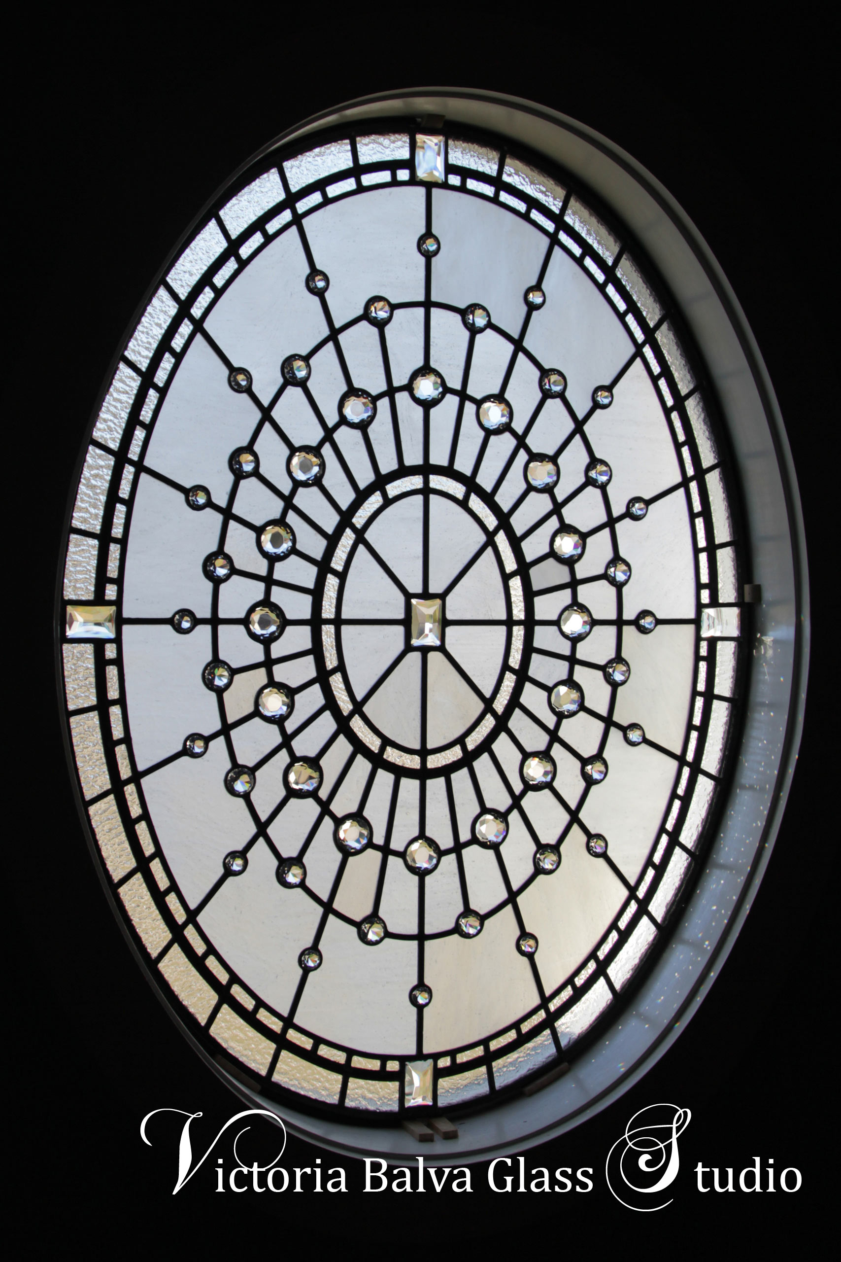 Spectacular oval stained leaded glass window w crystal diamond jewels for staircase of custom built residence in Washington DC. Glass diamond jewels refract the light into many tiny rainbows. Clear textured glass, various size glass diamonds, intricate linework. Stained glass oval window design by stained glass artist Victoria Balva