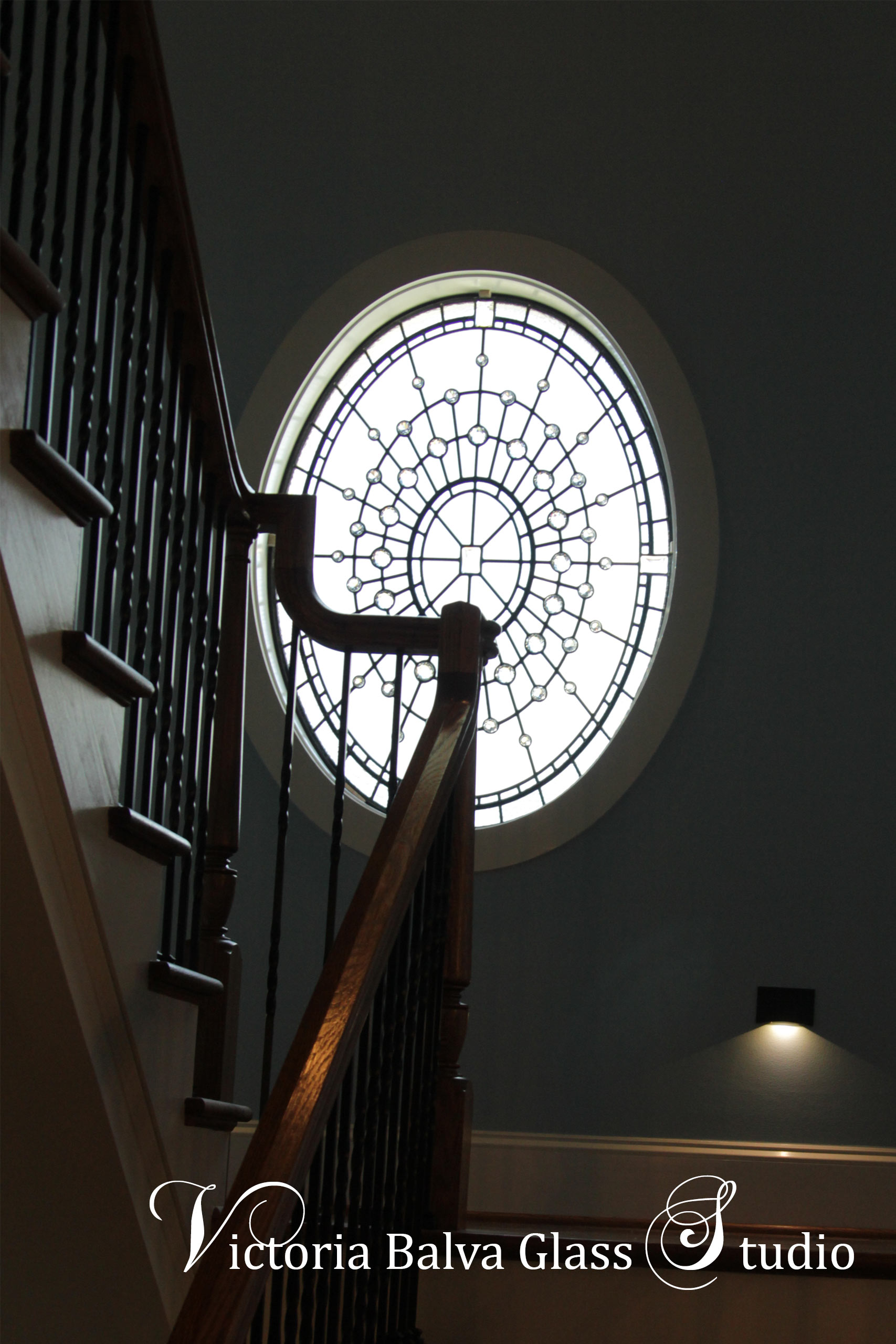 Spectacular oval stained glass window for a stair landing of a custom built residence