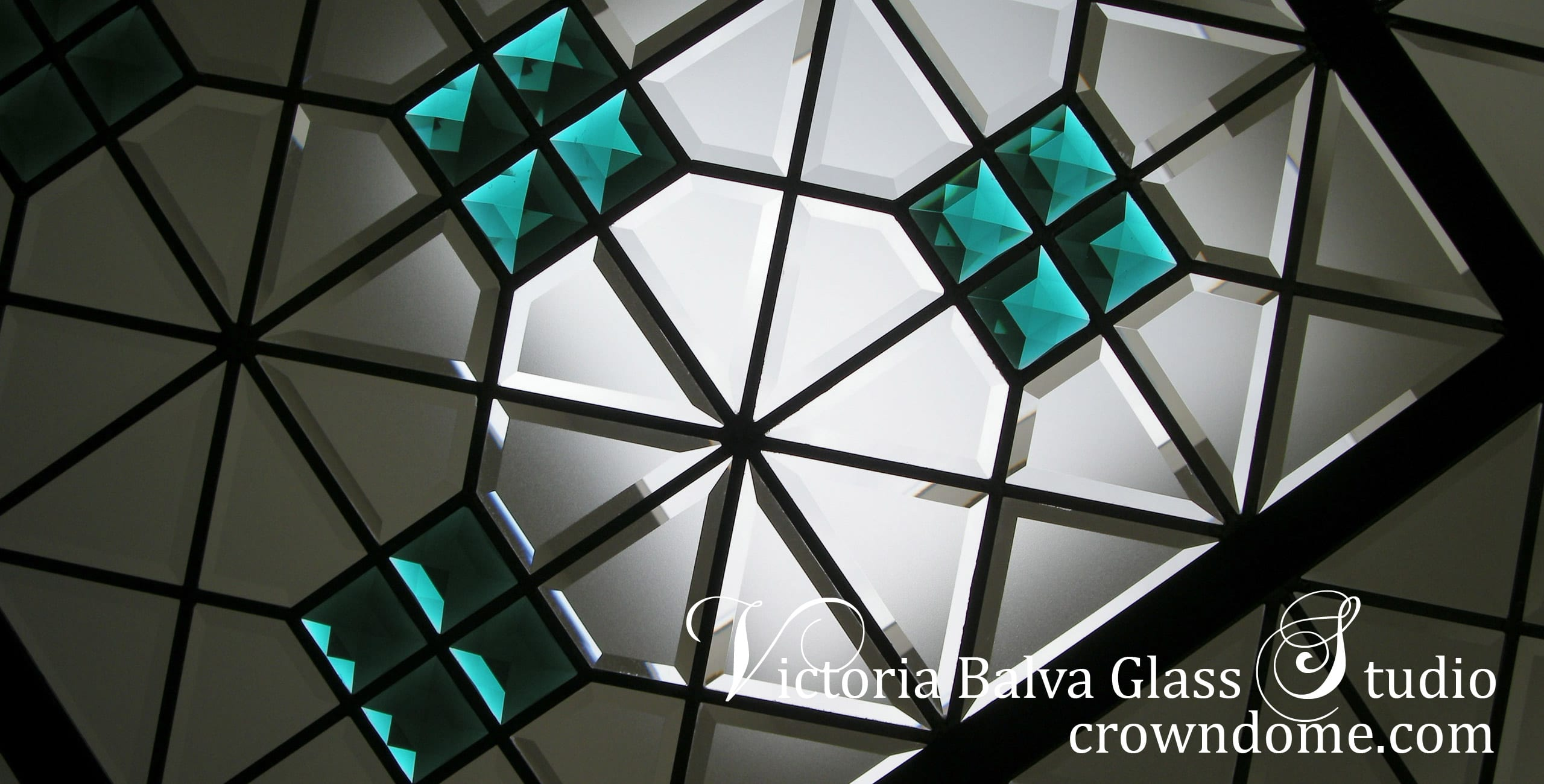 Eye-catching stained beveled leaded glass skylight ceiling with emerald accent jewels and colored beveled glass for a bathroom of a custom built luxury residence. Simple geometric stained leaded glass design with custom beveled glass and large emerald jewels by glass artist Victoria Balva