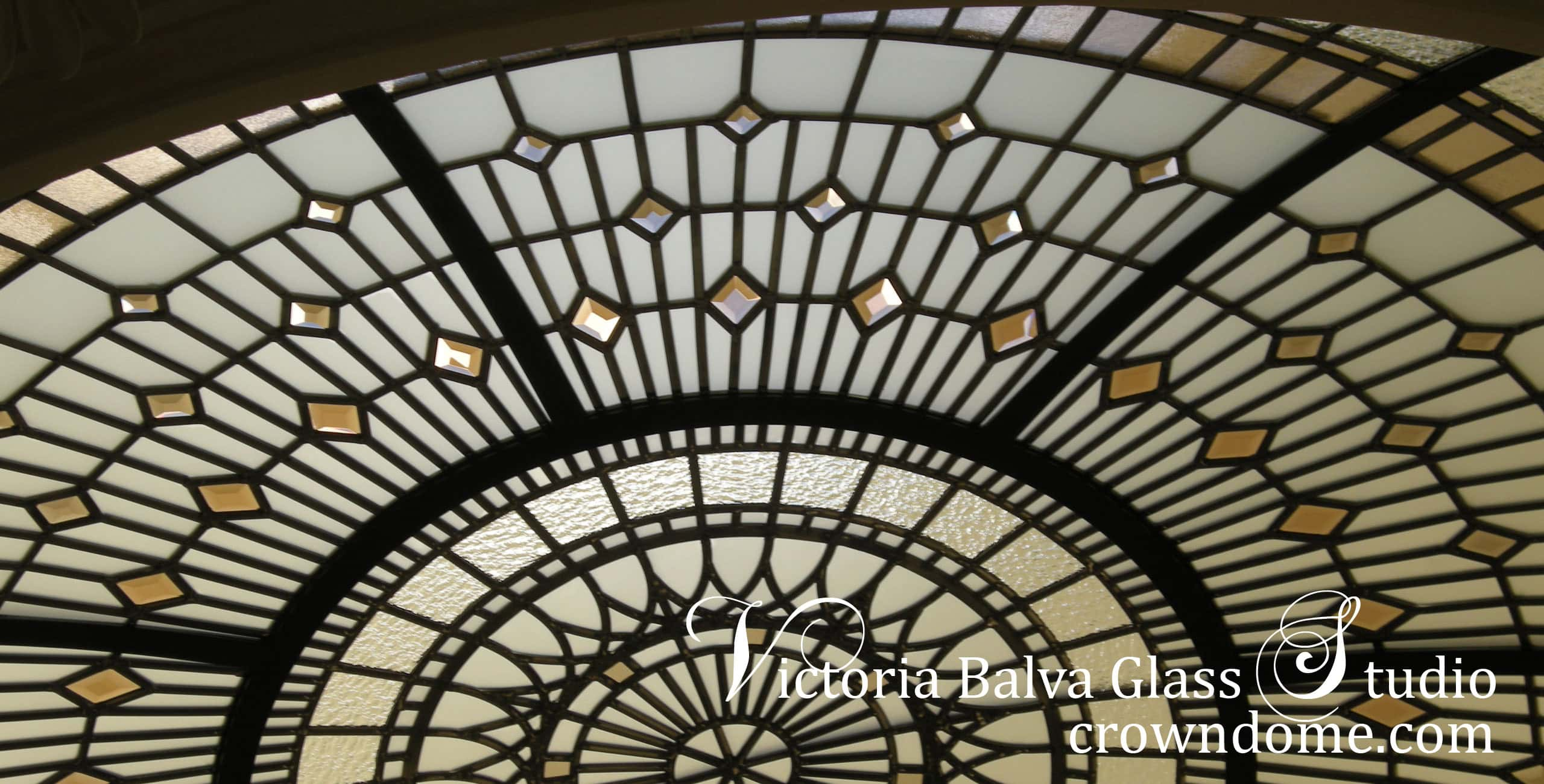 Stained beveled leaded glass dome detail with colored beveled glass and bronze textured glass for a foyer of a custom built residence. Warm colors of leaded glass dome in combination with blue sky color create dramatic colors combinations. Original leaded glass dome design by glass artist Victoria Balva