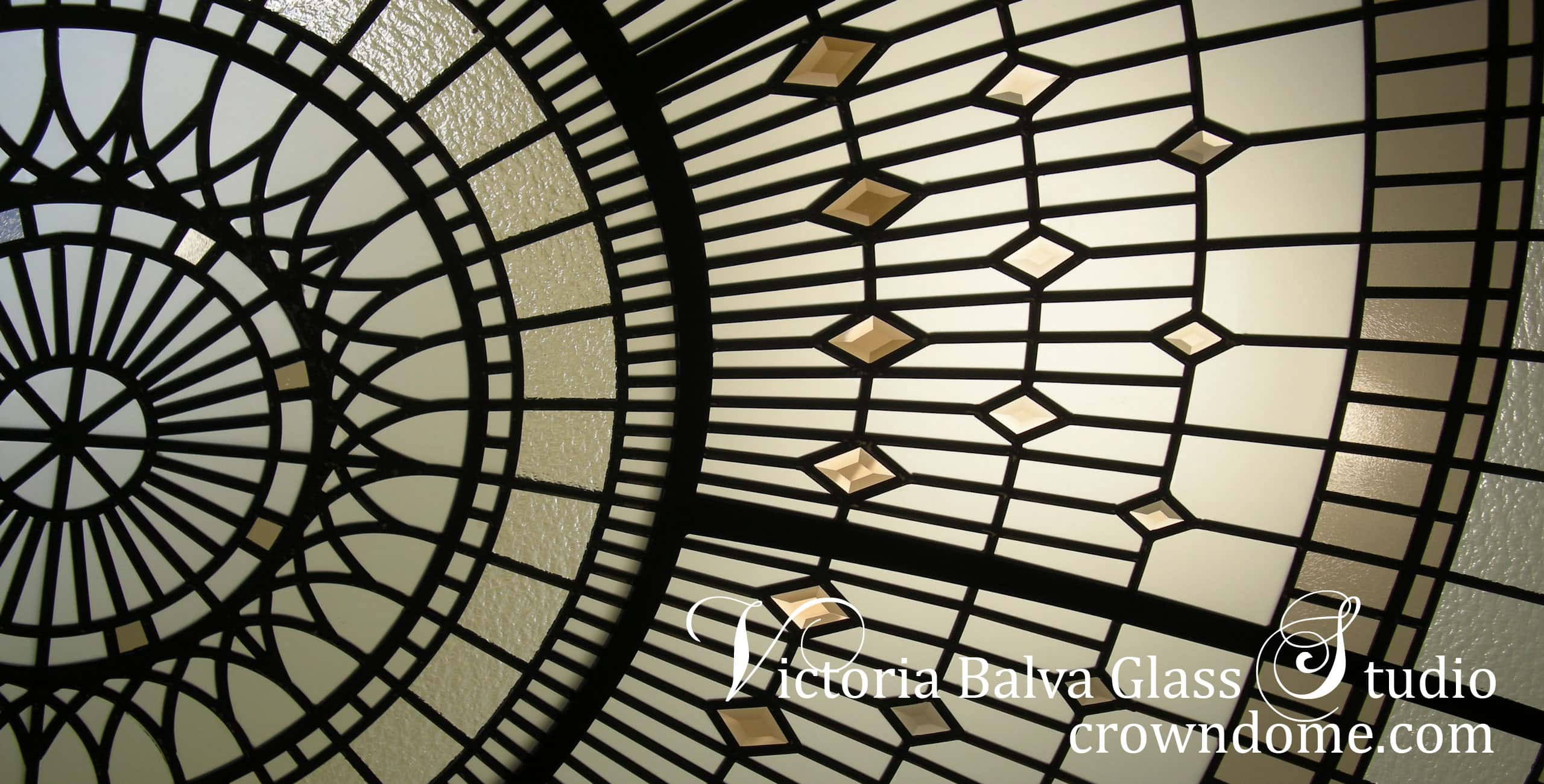 Close up leaded glass dome detail in sunshine. Stained beveled leaded glass dome detail with colored beveled glass and bronze textured glass for a foyer of a custom built residence. Warm colors of leaded glass dome in combination with blue sky color create dramatic colors combinations. Original leaded glass dome design by glass artist Victoria Balva