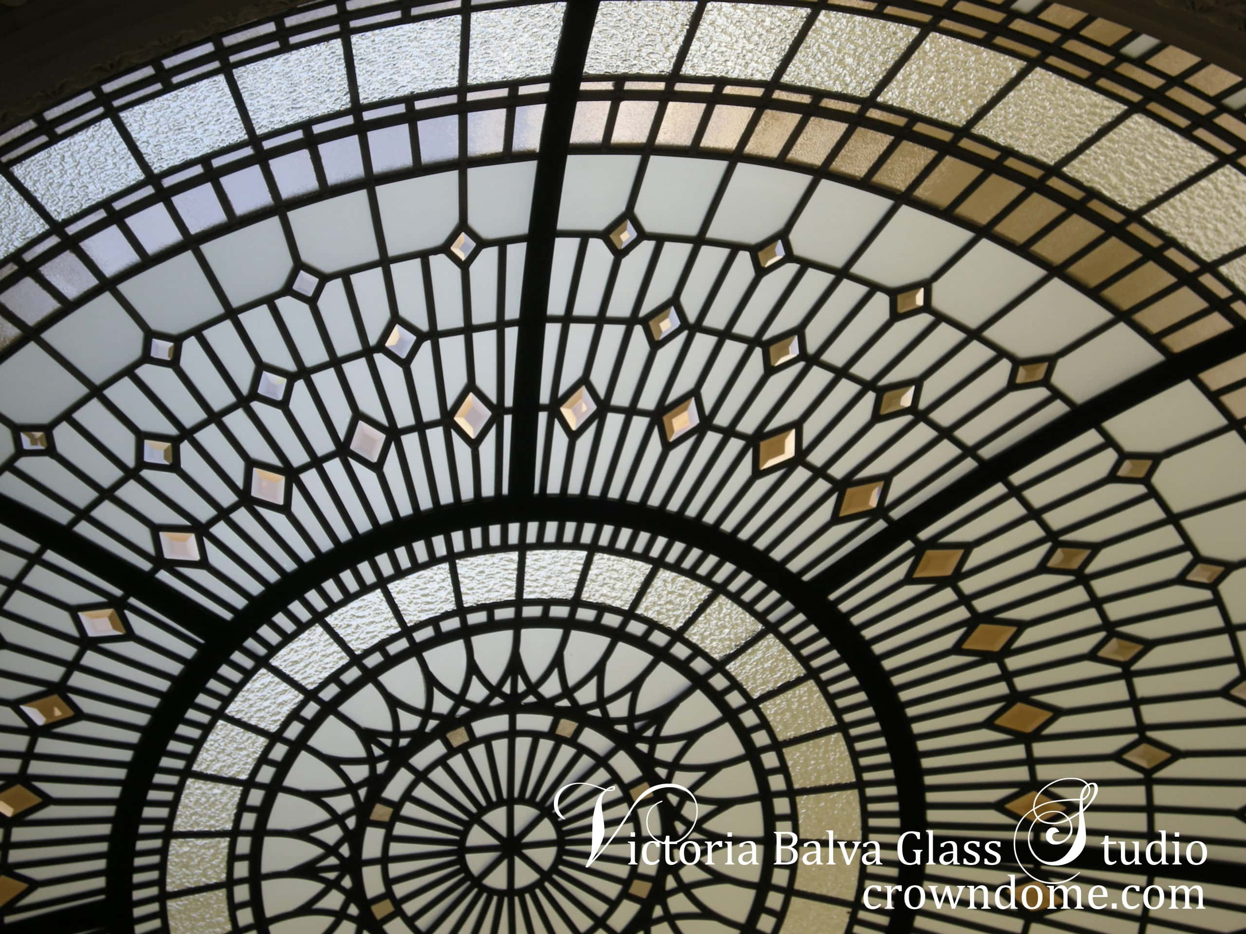 Detail of large 9 f diameter stained leaded glass dome. Stained beveled leaded glass dome with colored beveled glass and bronze textured glass for a foyer of a custom built residence. Warm colors of leaded glass dome in combination with blue sky color create dramatic colors combinations. Original leaded glass dome design by glass artist Victoria Balva