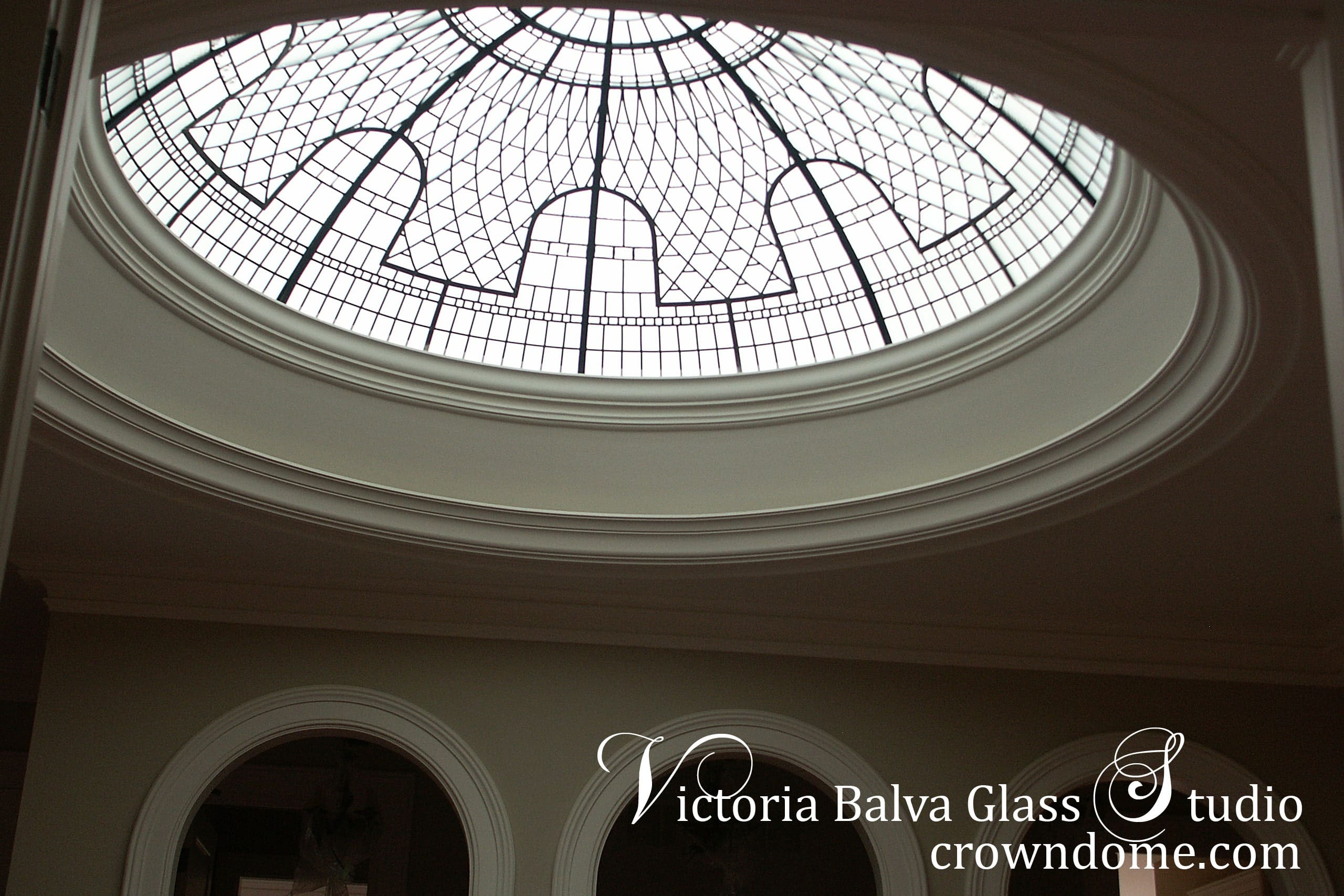 Large custom made leaded glass dome of a hallway of a private residence with clear textured glass, clear crystal jewels and beveled glass to provide light and style to the space below. Arch elements of the glass dome are in combination with hallway arches