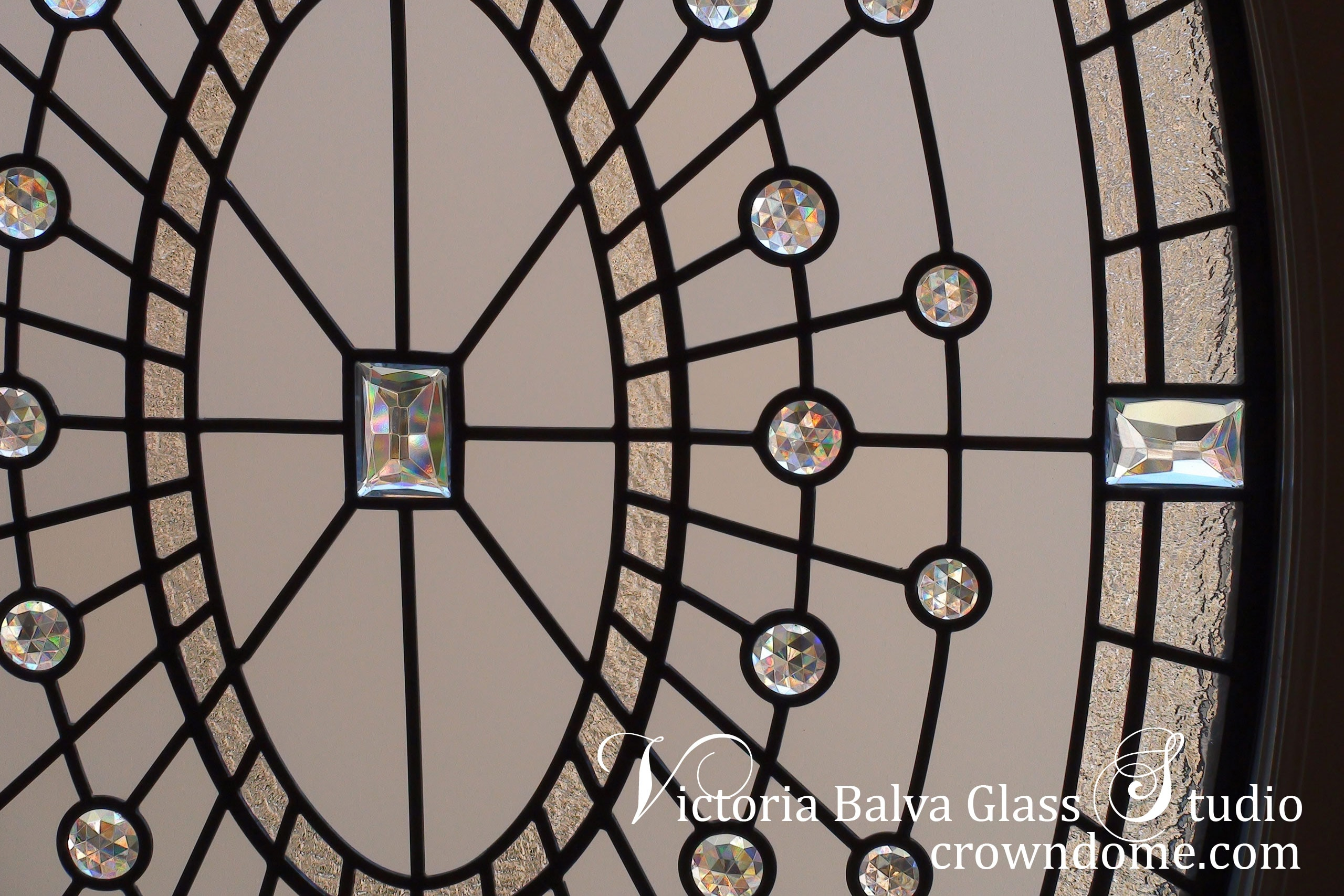 Large leaded glass oval window w monochromatic clear glass, accent jewels, and various clear textured glasses to create classically modern accent glass window. Leaded glass design by architectural glass artist Victoria Balva