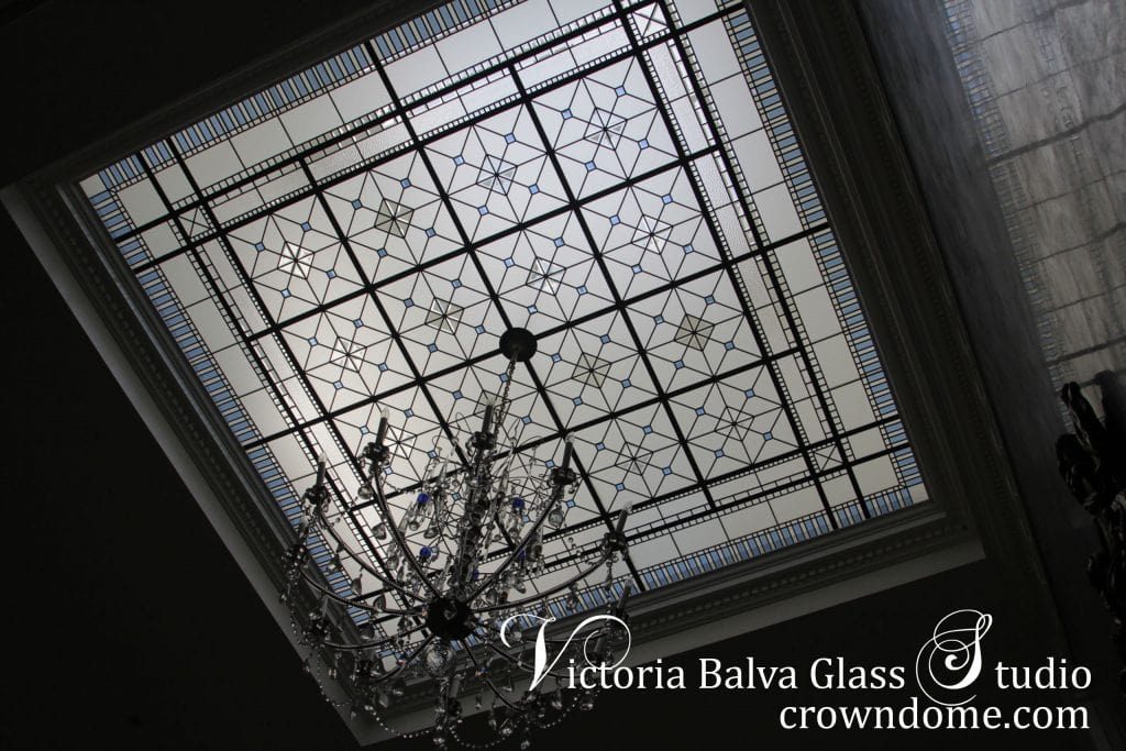 Beautiful stained leaded glass skylight ceiling with crystal chandelier hanging from a center of leaded glass ceiling. Double-height grand entrance foyer