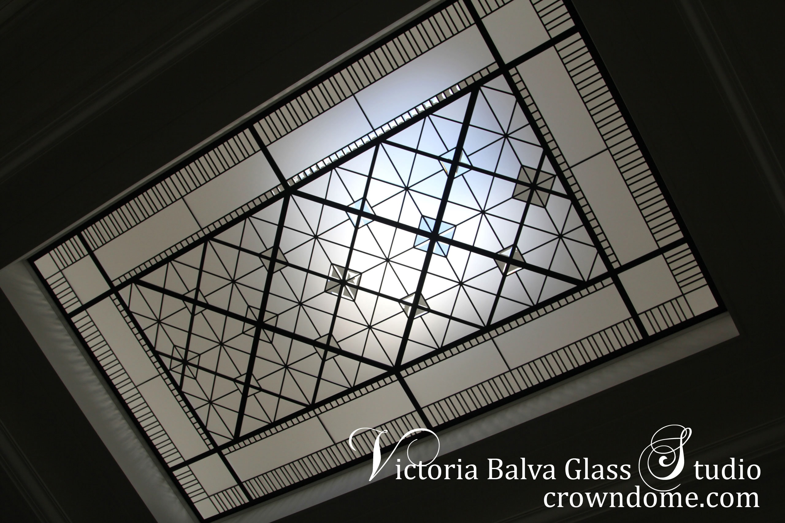 Geometric colorless leaded glass skylight ceiling design in simple geometric style with clear textured glass and clear beveled glass for a stairwell of custom built residence in Toronto. Original design by glass artist Victoria Balva