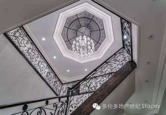 Custom octagon stained glass dome skylight with crystal chandelier above the staircase