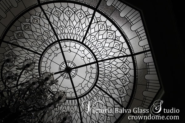 Octagon stained leaded glass domes ceiling with crystal chandelier suspended from the center of the glass dome