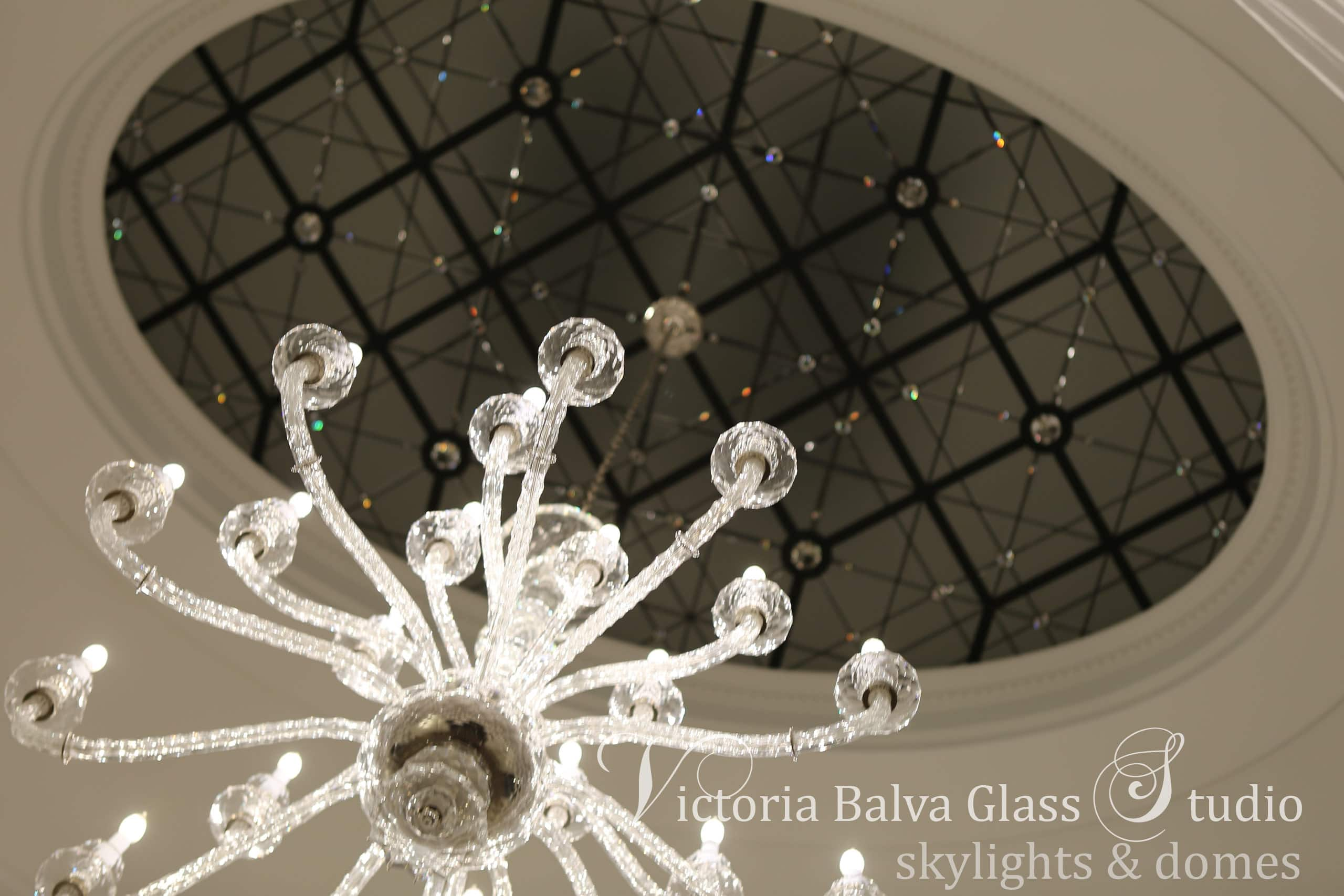 decorative stained glass ceiling at a night time with crystal chandelier in the custom built home