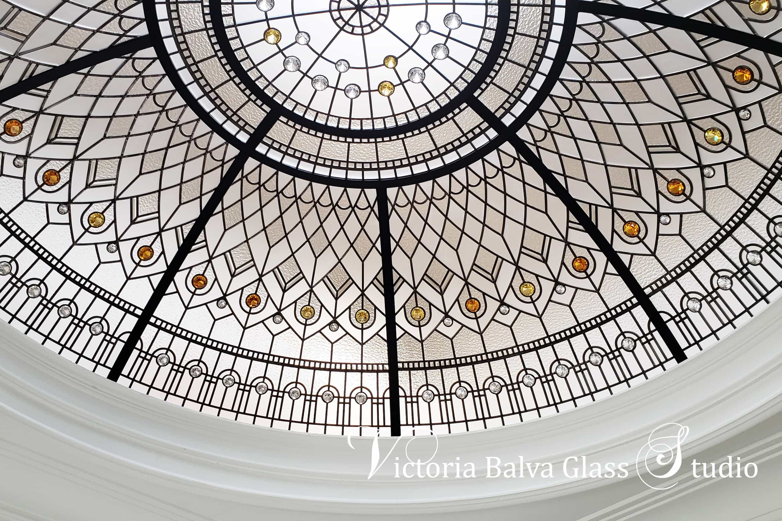 Large stained glass dome ceiling for a staircase of custom built house in Brampton. Clear textured glasses with pale coloured jewels.