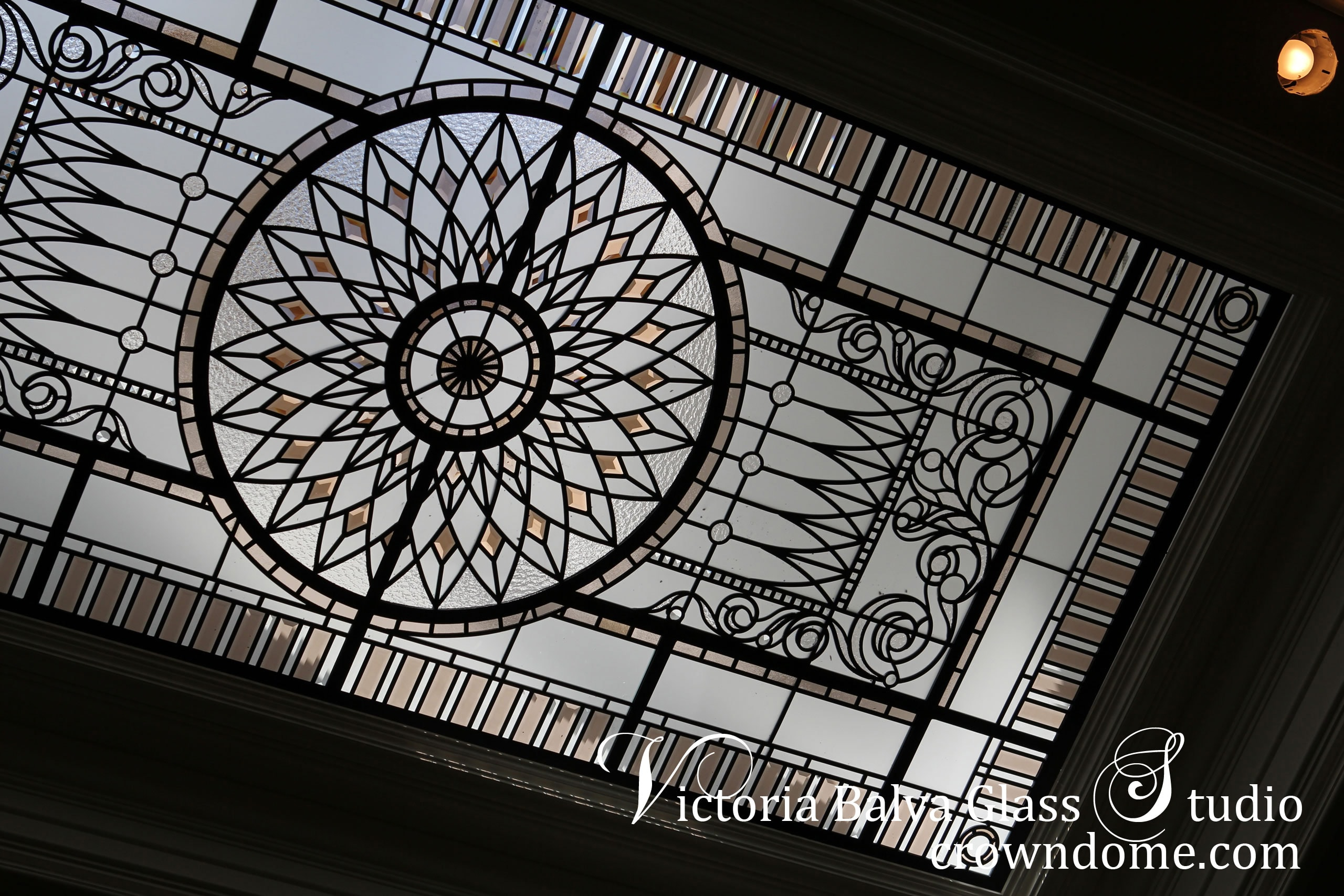 Stained leaded glass skylight ceiling Marion with pale colored beveled glass, acanthus ornamental border, clear textured glass for a stairwell of a custom built residence on Mississauga Rd. Luxury style is reflected in stained leaded glass skylight design