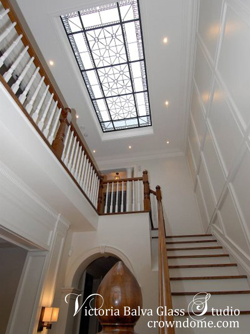 Large stained leaded glass skylight with custom hand bevelled glass to add art and natural light to a staircase hallway