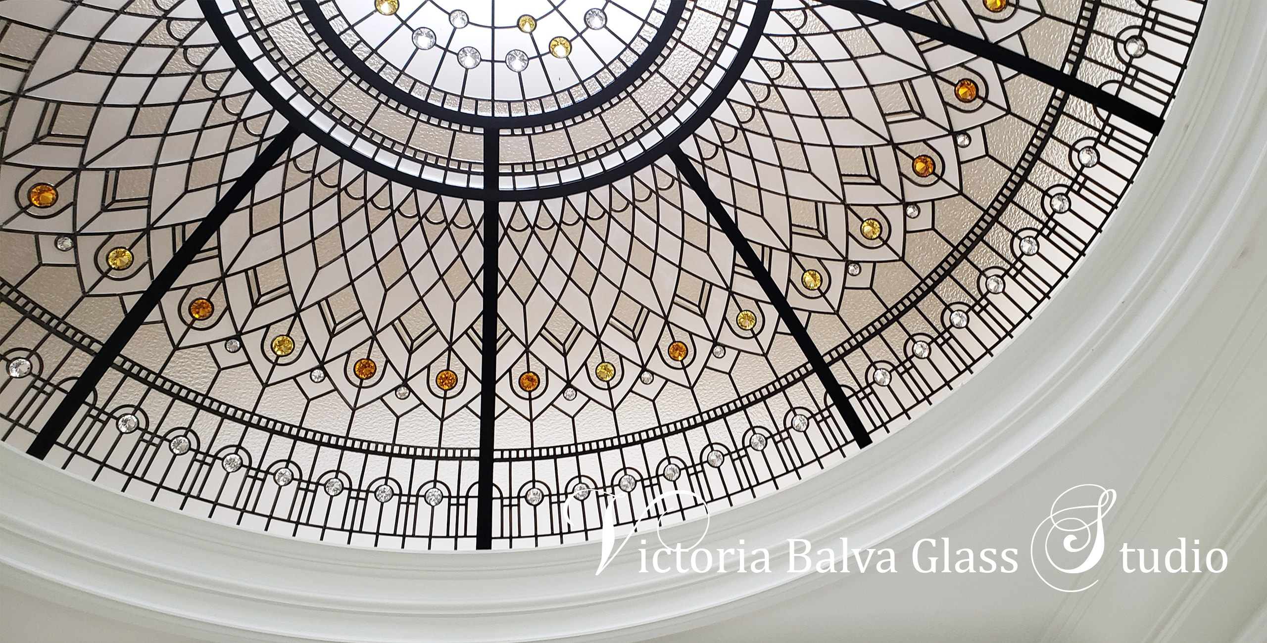 Stained glass dome with amber yellow crystal jewels made of clear textured glasses for grand entrance foyer with spiral staircase of custom built luxury house in Brampton
